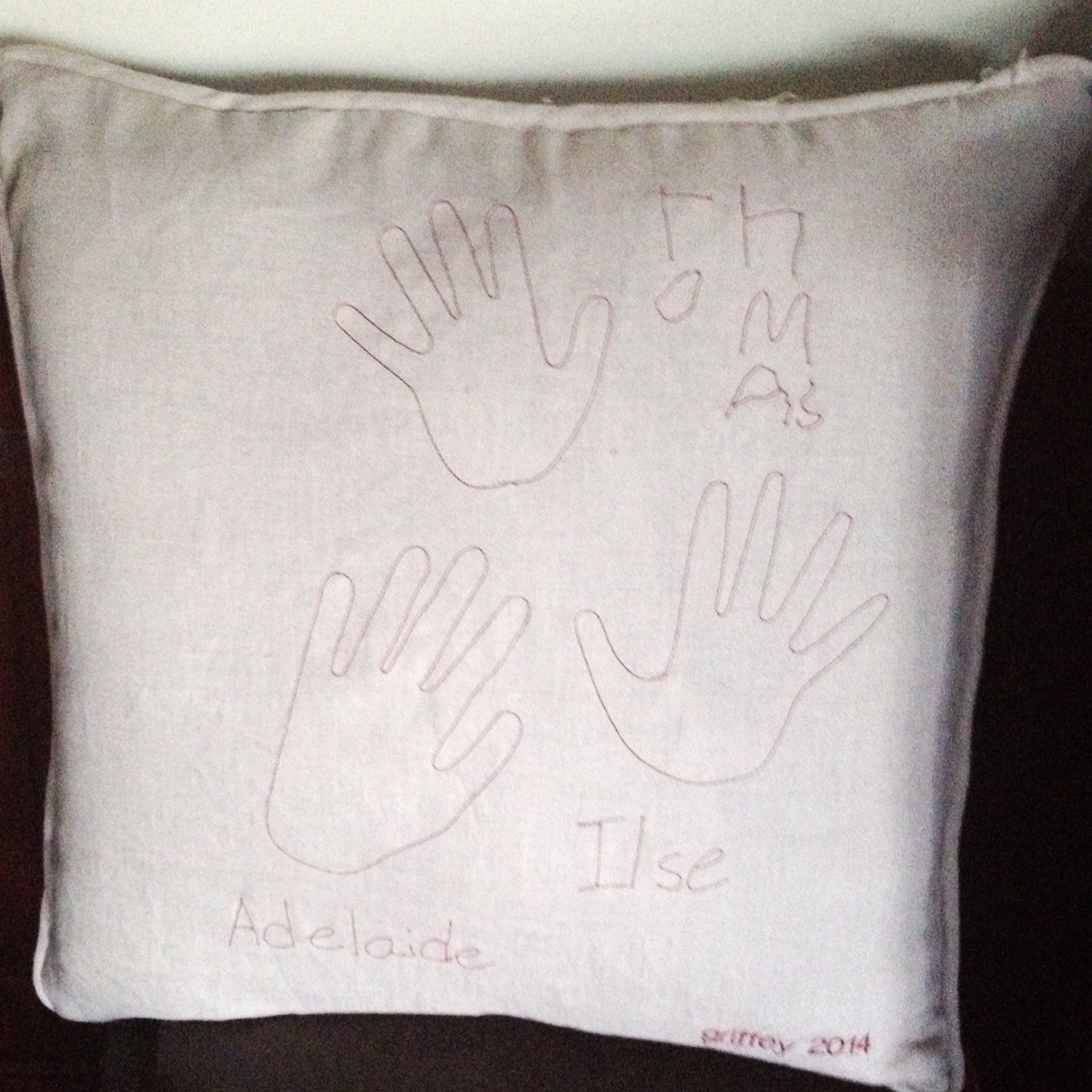 embroidered pillow with handprints