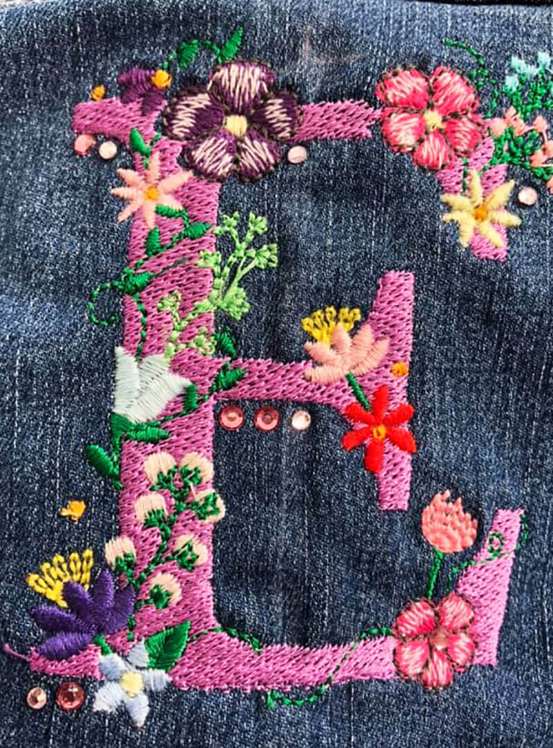 Single initial embroidered on denim